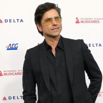 John Stamos in a black suit and sunglasses