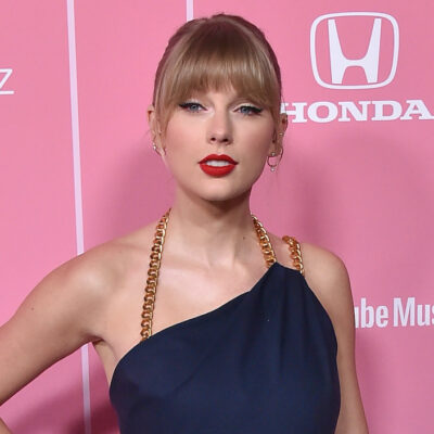 Taylor Swift smiling in a navy romper