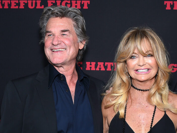 Kurt Russell in a suit smiling with Goldie Hawn in a black dress