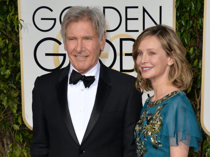 Harrison Ford in a tuxedo smiling with Calista Flockhart in a blue dress