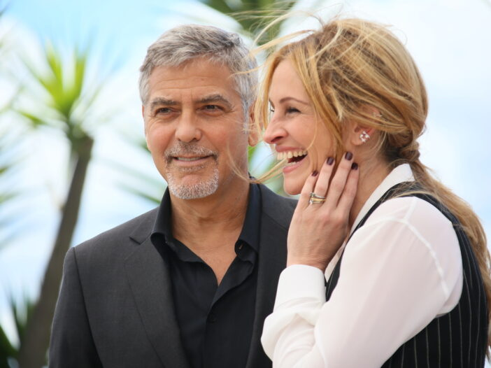 George Clooney in a suit with Julia Roberts in a white and black outfit
