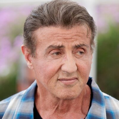 Sylvester Stallone wears a blue plaid shirt at a film festival