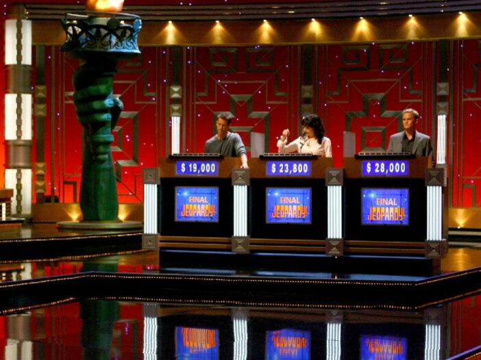 Celebrity contestants on Jeopardy! stand behind their podiums on set