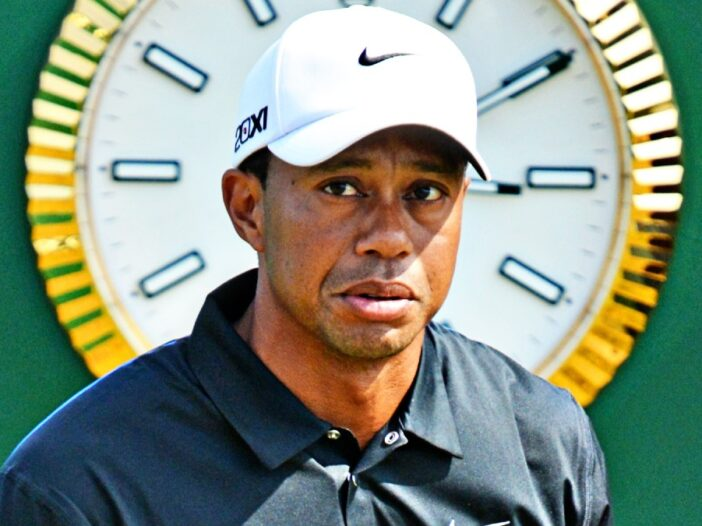 Tiger Woods wears a black golf shirt and white hat in front of a clock