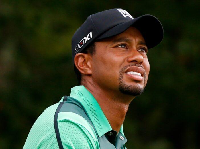 Tiger Woods wears a green shirt as he plays golf