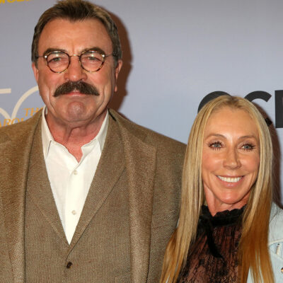 Tom Selleck in a brown suit, standing with Jillie Mack