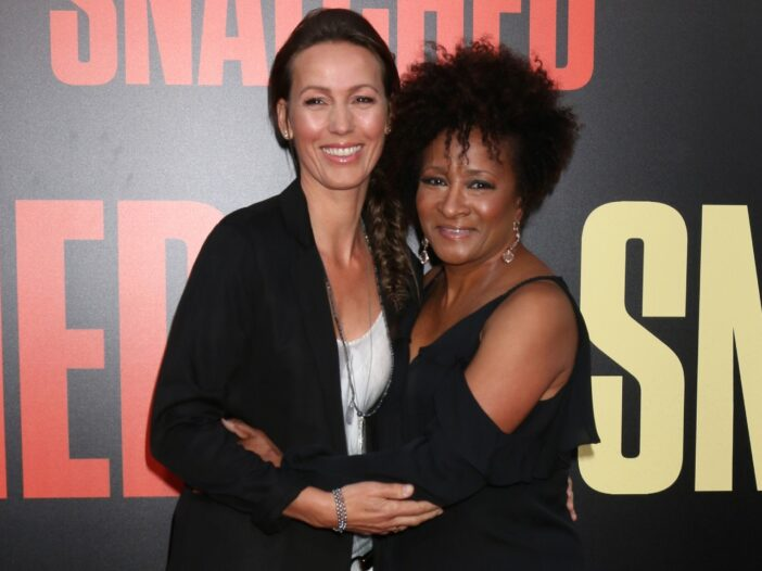 Wanda Sykes and her wife, Alex Sykes, both wearing black and hugging each other on the red carpet.