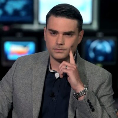 Ben Shapiro resting his finger on his face and wearing a grey suit.