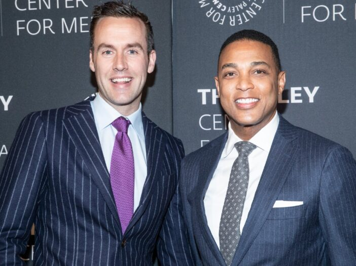 Don Lemon and his partner, Tim Malone, smiling at an event and wearing navy blue pin striped suits.