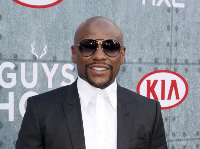 Floyd Mayweather wearing a black suit with a white shirt and tie.