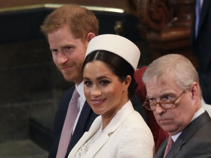 Prince Harry, Meghan Markle, and Prince Andrew sitting in a row