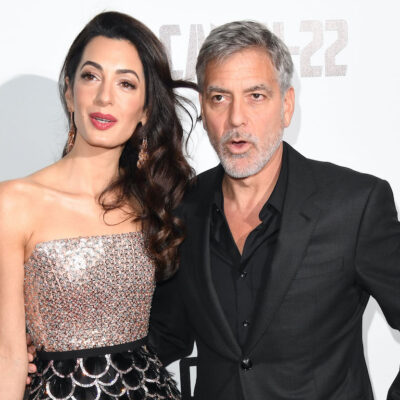 George Clooney in a suit with Amal Clooney in a silver dress
