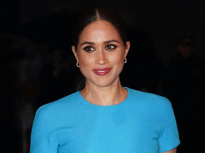 Meghan Markle smiling in a blue dress