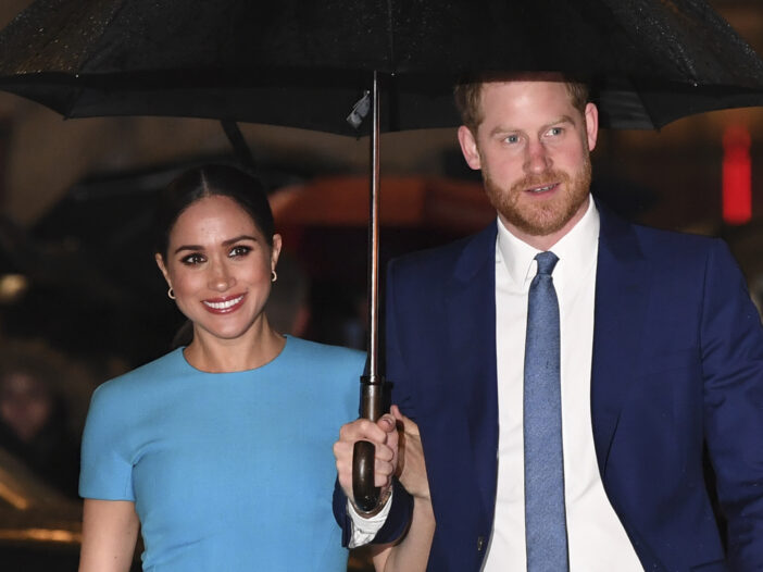 Prince Harry in a blue suit holding an umbrella for Meghan Markle in a blue dress
