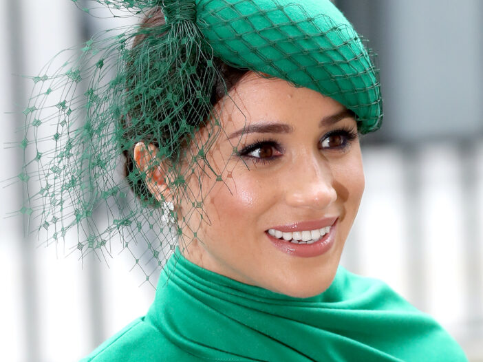 close up of Meghan Markle smiling in a green outfit