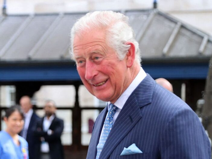 Prince Charles smiling in a navy suit