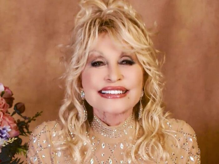 close up of Dolly Parton smiling in a gold dress