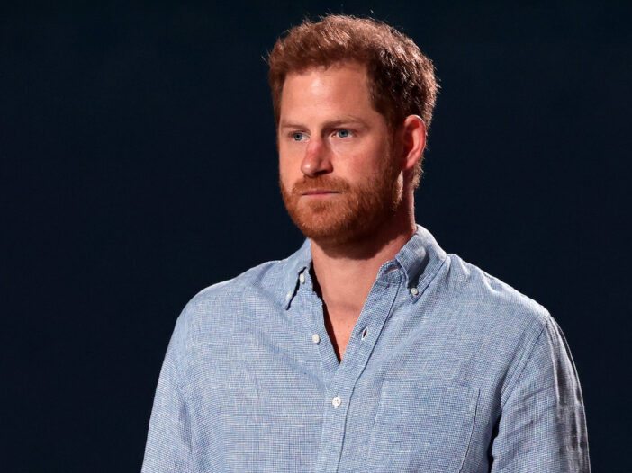 Prince Harry looking forward in a blue shirt