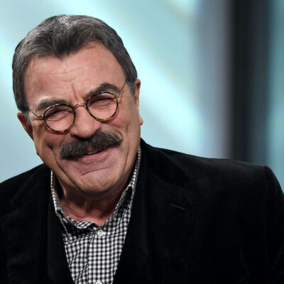 Tom Selleck smiling in a black jacket on stage