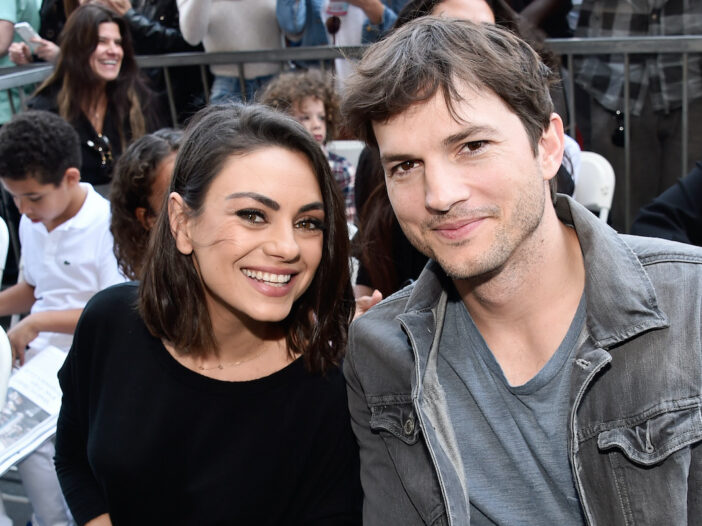 Ashton Kutcher in a jean jacket with Mila Kunis in a black top