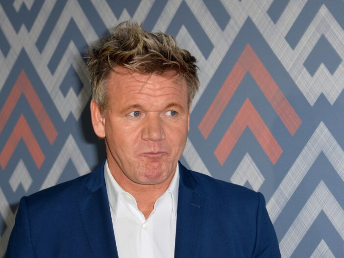 Gordon Ramsay making a silly scrunched face while wearing a navy blue suit.
