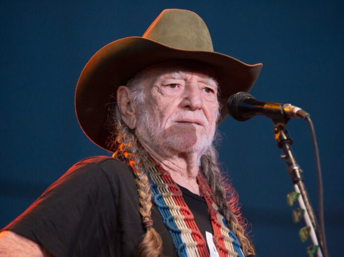 Willie Nelson wearing a black shirt and a green cowboy hat while performing on stage.