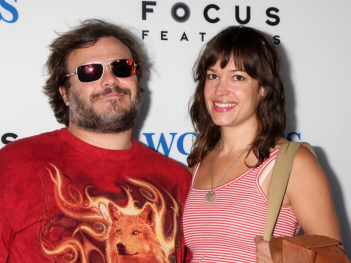 Jack Black wearing a red shirt with flames and a wolf on the front He's with his wife, Tanya Haden, who is wearing a red and white shirt.