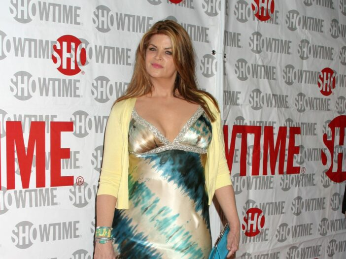 Kirstie Alley at a red carpet event wearing a blue and yellow dress with a yellow sweater.