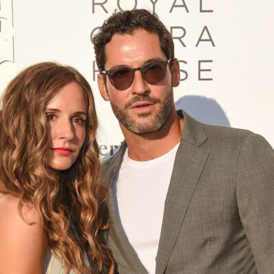 Tom Ellis in a grey suit with his wife, Meaghan Oppenheimer, who is wearing a green and beige dress.