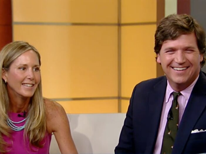 Tucker Carlson and his wife, Susan Andrews on the set of Fox News. He's wearing a navy blue suit, and she's wearing a pink dress.