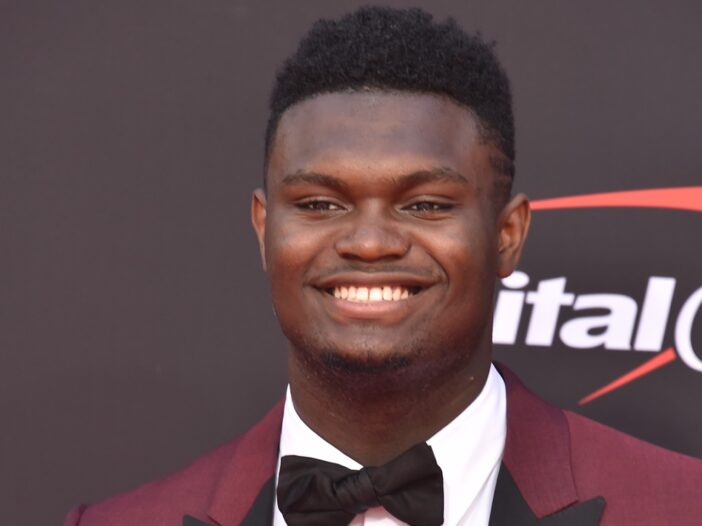 Zion Williamson smiling and wearing a red suit with a black bow tie.