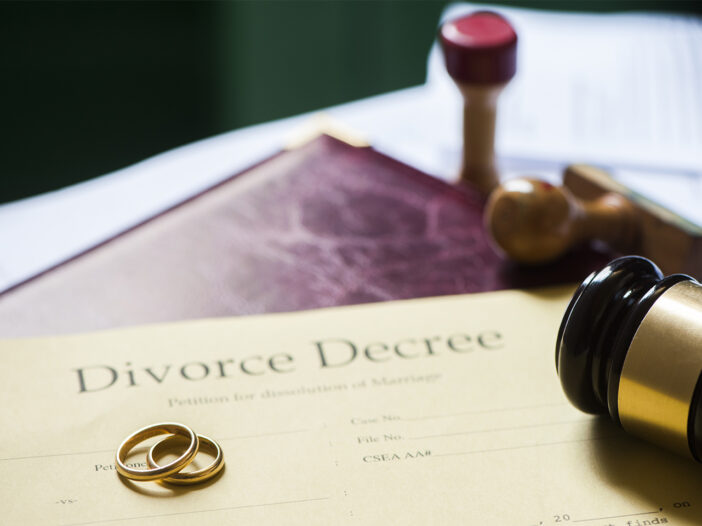 Divorce decree and wooden gavel, and rings.