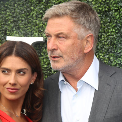 Hilaria and Alec Baldwin looking to their right in front of an ivy wall.