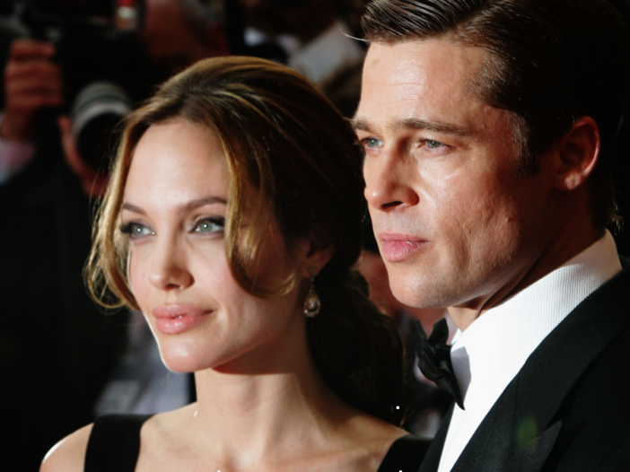 Angelina Jolie, in a black dress, poses for photos with Brad Pitt, in a black tux