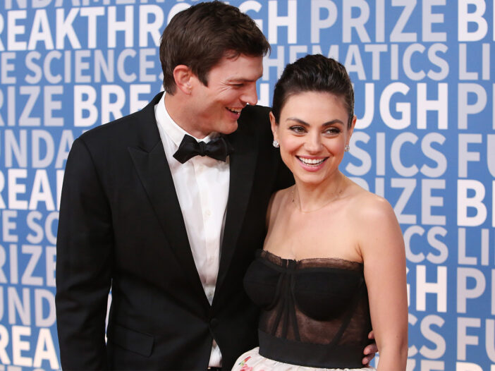 Ashton Kutcher laughing with Mila Kunis at a red carpet event