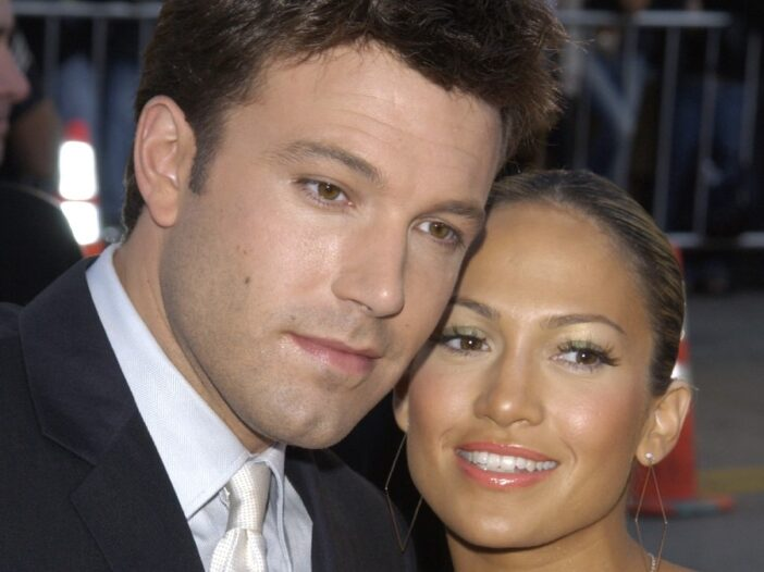 Ben Affleck, in a dark tux, cozies up to Jennifer Lopez, in a colorful dress, on the red carpet