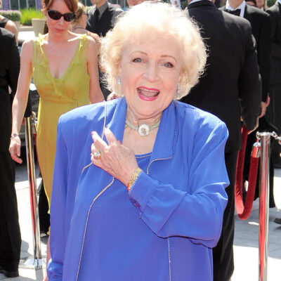 Betty White with her hand on her heart, wearing a blue outfit.