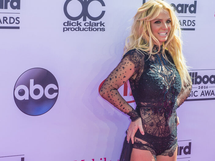 Britney Spears smiling in a shear black outfit