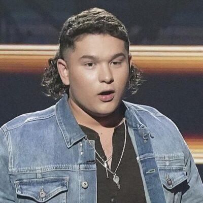 American Idol contestant Caleb Kennedy wears a blue denim jacket onstage