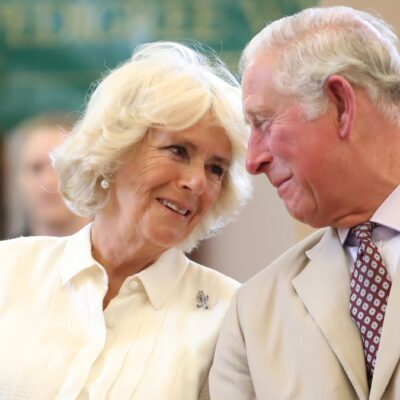Camilla Parker Bowles, in a white blouse, leans towards Prince Charles, in a khaki suit, who smiles at her