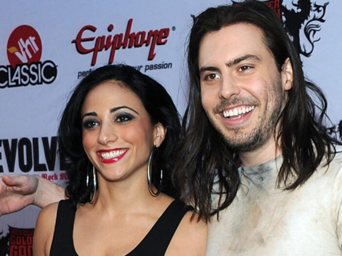 Cherie Lily, in a black leotard, stands with Andrew WK, in a grimy white t shirt, on the red carpet
