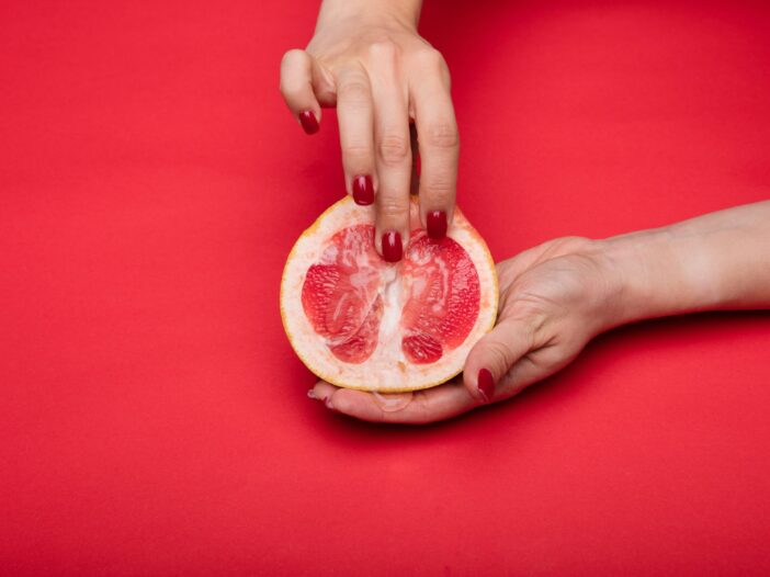 Cut grapefruit with a woman's hand in a sexually suggestive position/
