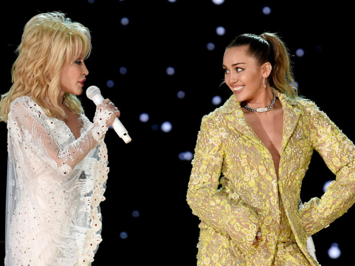 Dolly Parton on the left in white, performing on stage with Miley Cyrus, on the right in gold