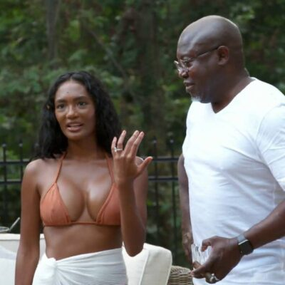 Falynn Guobadia wears a bathing suit as she stands with her now ex husband Simon, in a white t shirt, outdoors