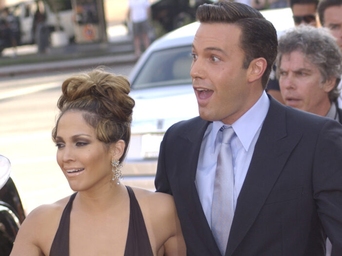 Ben Affleck, looking surprised, walking with Jennifer Lopez in 2003
