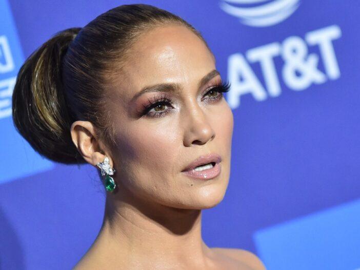 Jennifer Lopez wears a strapless dress against a blue backdrop