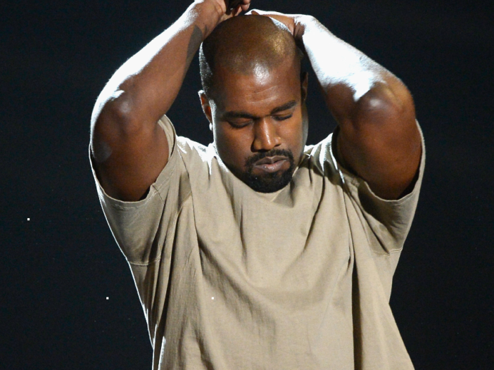 Kanye West holds his hands above his head while wearing a beige t shirt on stage