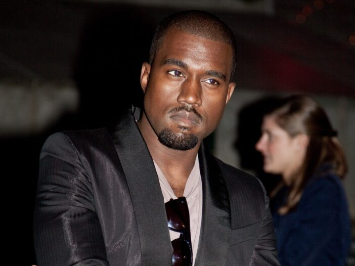 Kanye West wears a dark suit jacket over a t shirt and crosses his arms