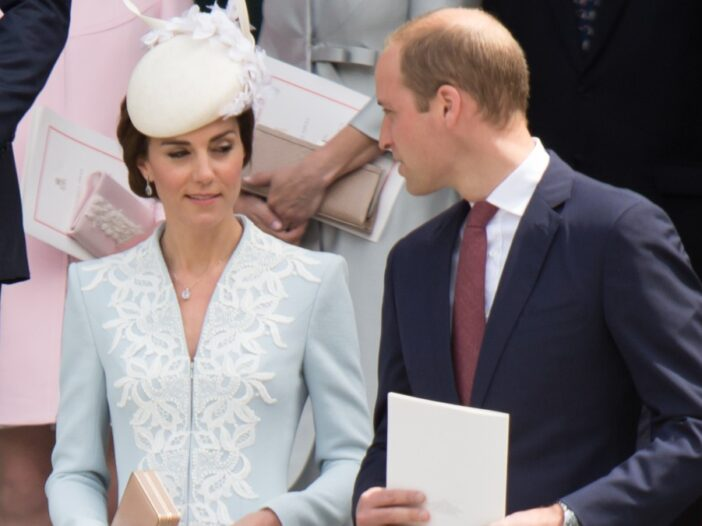 Kate Middleton, in blue, shares a look with her husband Prince William, in a dark suit