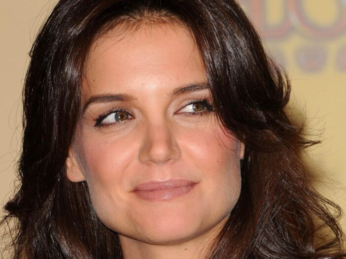 Katie Holmes looks to the side as she smiles slightly
